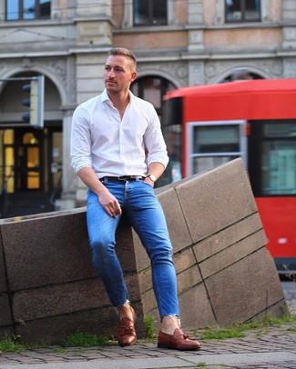 Cómo combinar: camisa de manga larga blanca, vaqueros pitillo azules, mocasín con borlas de cuero marrón