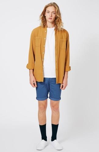 Cómo combinar: camisa de manga larga mostaza, camiseta con cuello circular blanca, pantalones cortos azules, tenis de cuero blancos