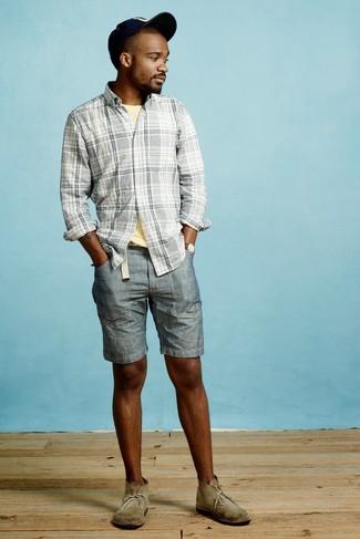 Cómo combinar: camisa de manga larga de tartán gris, camiseta con cuello circular amarilla, pantalones cortos vaqueros azules, botas safari de ante verde oliva