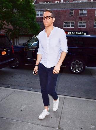 Cómo combinar: camisa de manga larga celeste, pantalón chino azul marino, tenis de cuero blancos, reloj de cuero negro
