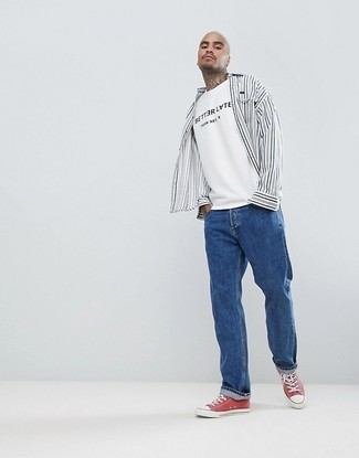 Cómo combinar: camisa de manga larga de rayas verticales en blanco y negro, camiseta con cuello circular estampada en blanco y negro, vaqueros azules, tenis de lona rojos