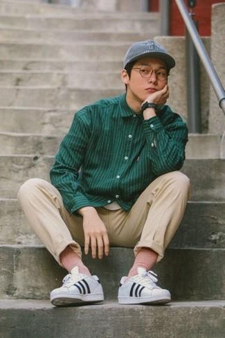 Cómo combinar: camisa de manga larga de rayas verticales verde oscuro, pantalón chino en beige, tenis de cuero de rayas horizontales en blanco y negro, gorra de béisbol gris