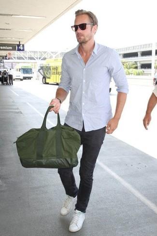 Cómo combinar: camisa de manga larga celeste, pantalón chino negro, tenis de cuero blancos, bolsa de viaje de lona verde oliva