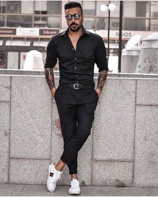 Cómo combinar: camisa de manga larga negra, pantalón chino negro, tenis de cuero estampados blancos, correa de cuero negra