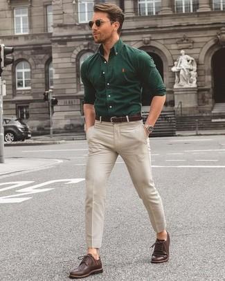 Cómo combinar: camisa de manga larga verde oscuro, pantalón chino en beige, zapatos brogue de cuero en marrón oscuro, correa de cuero en marrón oscuro