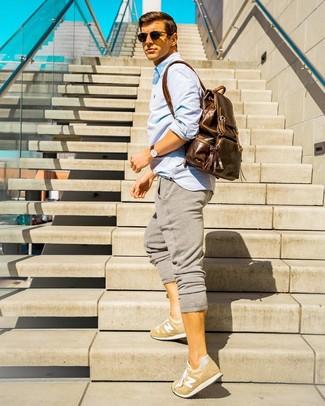 Cómo combinar: camisa de manga larga celeste, pantalón de chándal gris, tenis marrón claro, mochila de cuero marrón