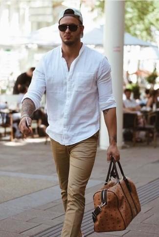 Cómo combinar: camisa de manga larga blanca, pantalón de vestir en beige, bolsa de viaje de cuero marrón, gorra de béisbol blanca