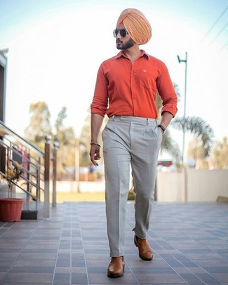 Cómo combinar: camisa de manga larga naranja, pantalón de vestir en beige, botines chelsea de cuero marrónes, gafas de sol negras