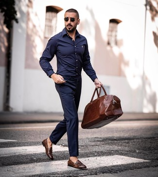 Cómo combinar: camisa de manga larga azul marino, pantalón de vestir azul marino, zapatos con doble hebilla de cuero marrónes, bolsa de viaje de cuero marrón