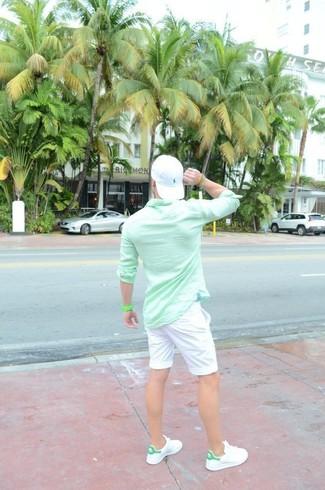 Cómo combinar: camisa de manga larga en verde menta, pantalones cortos blancos, tenis de cuero blancos, gorra de béisbol blanca