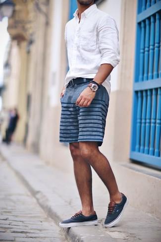 Cómo combinar: camisa de manga larga de lino blanca, pantalones cortos de rayas horizontales azules, zapatillas plimsoll azul marino, correa de lona azul marino