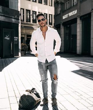 Cómo combinar: camisa de manga larga blanca, vaqueros desgastados grises, botas safari de ante grises, bolsa de viaje de cuero estampada en marrón oscuro