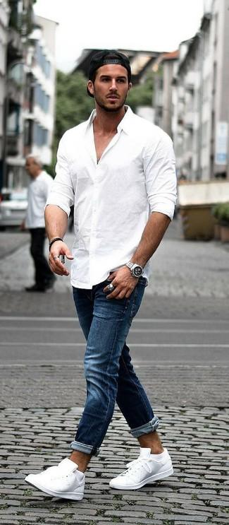 Cómo combinar: camisa de manga larga blanca, vaqueros azul marino, tenis de cuero blancos, gorra de béisbol negra