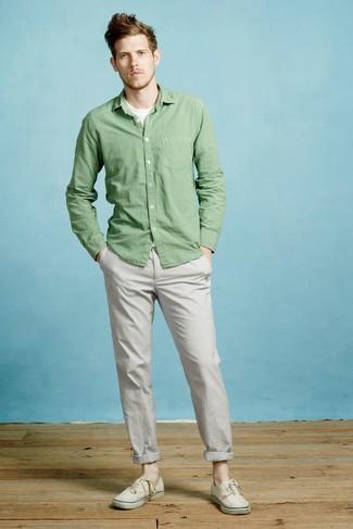 Cómo combinar: camisa de manga larga verde, camiseta con cuello circular blanca, pantalón chino gris, tenis de lona en beige