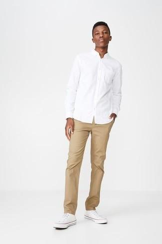 Cómo combinar: camisa de vestir blanca, pantalón chino marrón claro, tenis de lona blancos