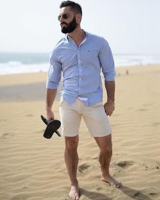 Cómo combinar: camisa de vestir celeste, pantalones cortos en beige, sandalias de goma negras, gafas de sol negras