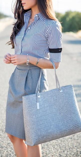 Cómo combinar: camisa de vestir de rayas verticales en blanco y azul marino, falda lápiz gris, bolsa tote de cuero con print de serpiente gris, pulsera plateada