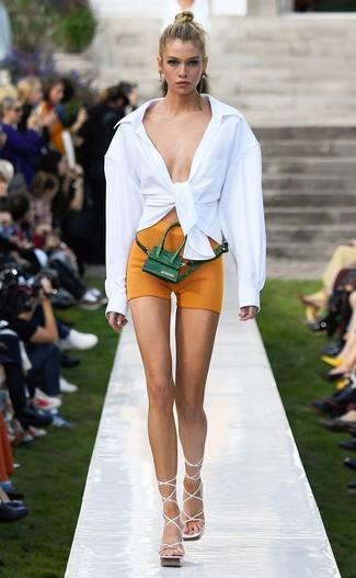 Cómo combinar: camisa de vestir blanca, mallas ciclistas mostaza, sandalias de tacón de cuero blancas, riñonera de cuero verde oscuro