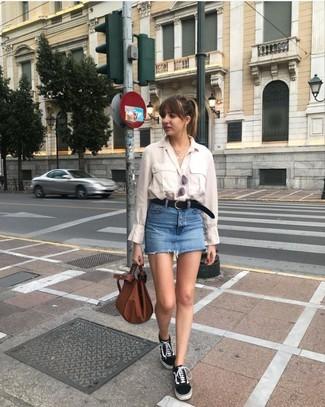 Cómo combinar: camisa de vestir en beige, minifalda vaquera azul, tenis de lona en negro y blanco, bolsa tote de cuero marrón