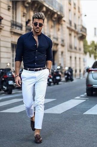 Cómo combinar: camisa de vestir azul marino, pantalón chino blanco, mocasín con borlas de cuero en marrón oscuro, correa de cuero tejida en marrón oscuro