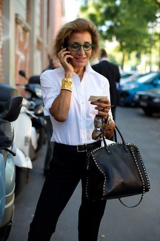Cómo combinar: camisa de vestir blanca, pantalón de pinzas negro, bolsa tote de cuero con tachuelas negra, correa de cuero negra