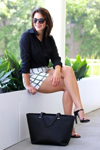 Una camisa de vestir negra y unos pantalones cortos a cuadros blancos y negros son el combo perfecto para llamar la atención por una buena razón. Complementa tu atuendo con sandalias de tacón de cuero negras.