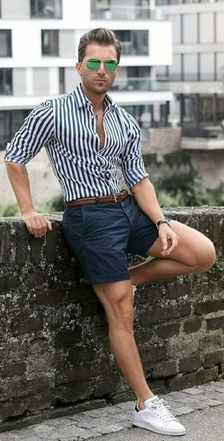 Cómo combinar: camisa de vestir de rayas verticales en blanco y azul marino, pantalones cortos azul marino, tenis blancos, correa de cuero marrón
