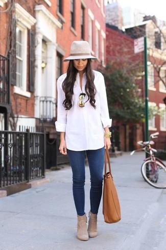 Cómo combinar: camisa de vestir blanca, vaqueros pitillo azules, botines de ante en beige, bolsa tote de cuero en tabaco