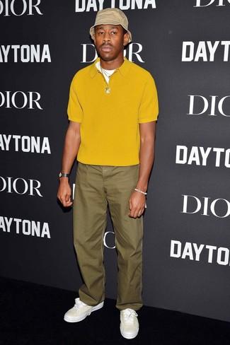 Cómo combinar: camisa polo mostaza, pantalón chino verde oliva, tenis de cuero blancos, gorro de pescador en beige