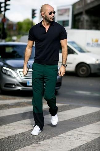 Look de moda: Camisa polo negra, Pantalón chino verde oscuro, Tenis blancos, Gafas de sol negras