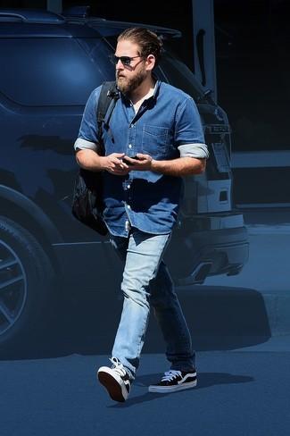 Cómo combinar: camisa vaquera azul, vaqueros celestes, tenis de lona en negro y blanco, mochila azul marino