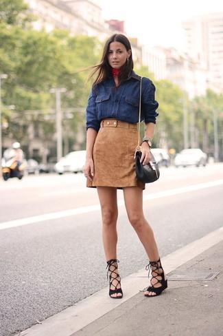 Cómo combinar: camisa vaquera azul marino, minifalda de ante marrón claro, sandalias romanas de ante negras, bolso bandolera de cuero negro