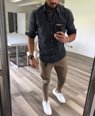 Cómo combinar: camisa vaquera en gris oscuro, pantalón chino marrón, zapatillas plimsoll blancas, reloj negro