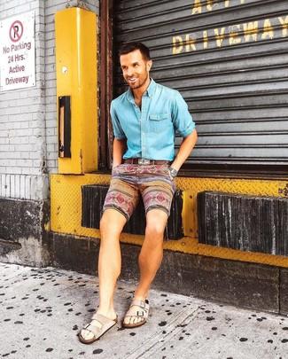 Cómo combinar: camisa vaquera celeste, pantalones cortos estampados en multicolor, sandalias de ante en beige, correa de cuero marrón