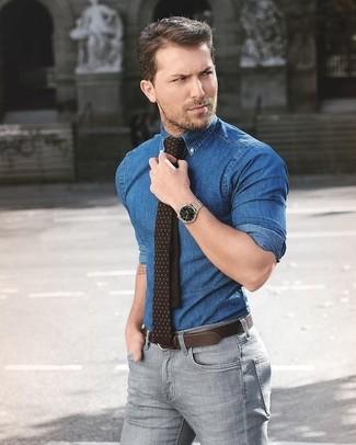 Cómo combinar: camisa vaquera azul, vaqueros pitillo grises, corbata a lunares en marrón oscuro, correa de cuero en marrón oscuro