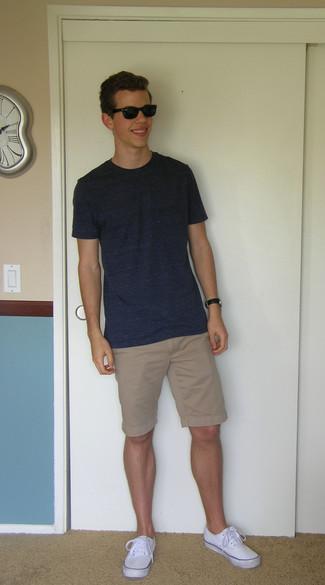 Cómo combinar: camiseta con cuello circular azul marino, pantalones cortos marrón claro, zapatillas plimsoll blancas
