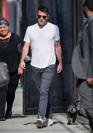 Cómo combinar: camiseta con cuello circular blanca, pantalón chino en gris oscuro, tenis de cuero blancos, gafas de sol en marrón oscuro