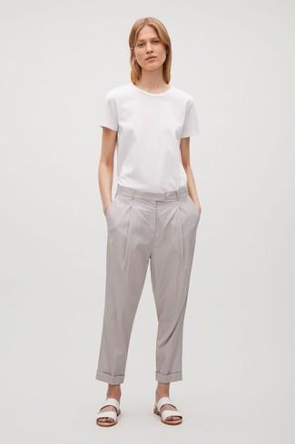 Cómo combinar: camiseta con cuello circular blanca, pantalón chino gris, sandalias planas de cuero blancas