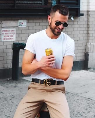 Cómo combinar: camiseta con cuello circular blanca, pantalón chino marrón claro, correa de cuero negra, gafas de sol negras