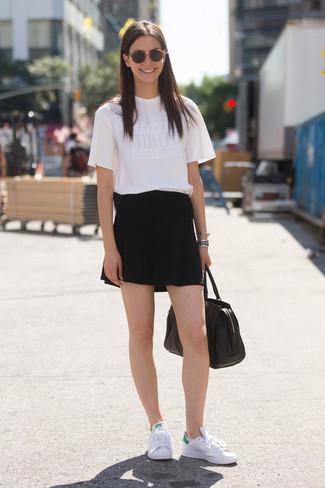 Cómo combinar: camiseta con cuello circular blanca, pantalones cortos negros, tenis de cuero blancos, bolsa tote de cuero negra