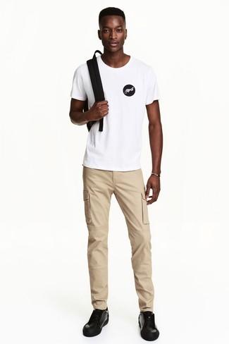 Cómo combinar: camiseta con cuello circular estampada en blanco y negro, pantalón chino marrón claro, tenis de cuero negros, mochila negra