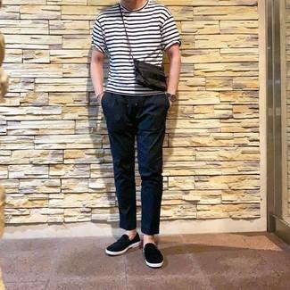 Cómo combinar: camiseta con cuello circular de rayas horizontales en blanco y negro, pantalón chino negro, zapatillas slip-on negras, reloj de cuero azul marino
