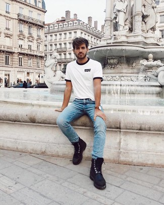 Cómo combinar: camiseta con cuello circular estampada en blanco y negro, vaqueros celestes, botas casual de cuero negras, reloj de cuero marrón