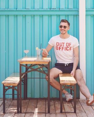 Cómo combinar: camiseta con cuello circular estampada en blanco y rojo, shorts de baño azul marino, deportivas en beige, gafas de sol marrónes