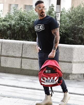 Cómo combinar: camiseta con cuello circular estampada en negro y blanco, vaqueros pitillo en gris oscuro, botines chelsea de ante en beige, mochila estampada roja