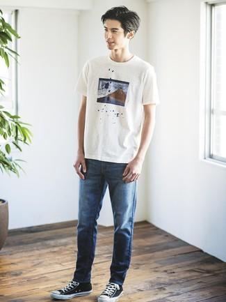 Cómo combinar: camiseta con cuello circular estampada blanca, vaqueros azul marino, tenis de lona en negro y blanco