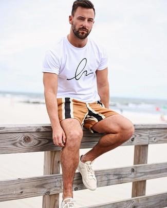 Cómo combinar: camiseta con cuello circular estampada en blanco y negro, pantalones cortos en multicolor, tenis de lona en beige