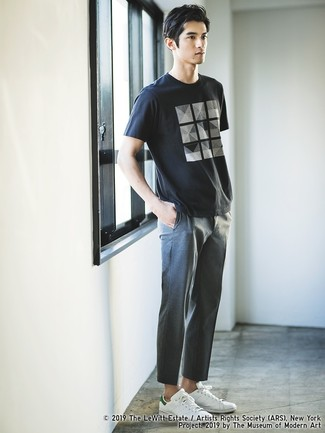 Cómo combinar: camiseta con cuello circular estampada en negro y blanco, pantalón chino gris, tenis de cuero blancos
