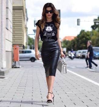 Cómo combinar: camiseta con cuello circular estampada en negro y blanco, falda lápiz de cuero negra, zapatos de tacón de cuero negros, cartera de cuero blanca