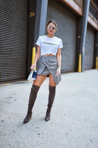 Cómo combinar: camiseta con cuello circular estampada en blanco y negro, falda línea a gris, botas sobre la rodilla de ante en marrón oscuro, cartera sobre de cuero en blanco y negro
